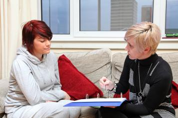 a young lady talking to their support worker about their mental health