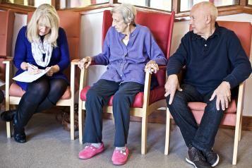 Seated elderly patients and staff with clipboard