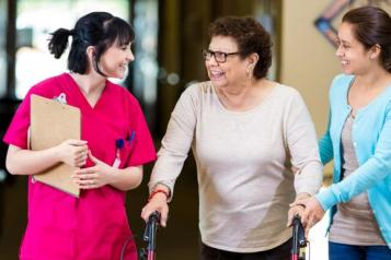 patient with mobility aid and relative talking to nurse