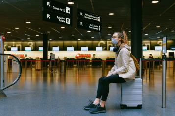 woman sitting in airport with face mask