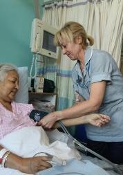 Nurse at patient's bedside on hospital ward